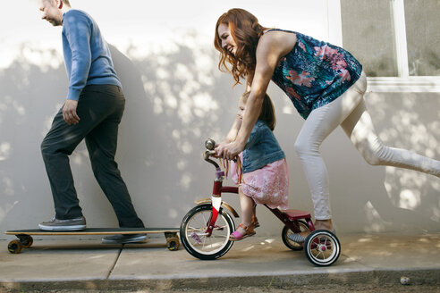 Girl riding tricycle with mother while father skateboarding at backyard - CAVF21396