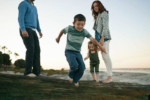 Family looking at boy jumping on rock while standing against clear sky - CAVF21426