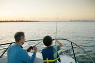 Father and son fishing on boat - CAVF21432