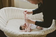 Cropped image of mother wearing sweater to baby lying in crib - CAVF21489