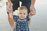 Portrait of cute girl holding father's hands while standing at beach - CAVF21558