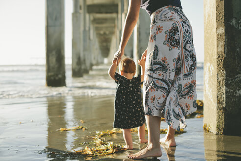 Low section of woman assisting daughter to walk at beach on sunny day - CAVF21561