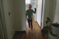 Portrait of smiling boy by doorway home - CAVF21606