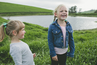 Cheerful girl standing with sister on grassy field by lake - CAVF21729