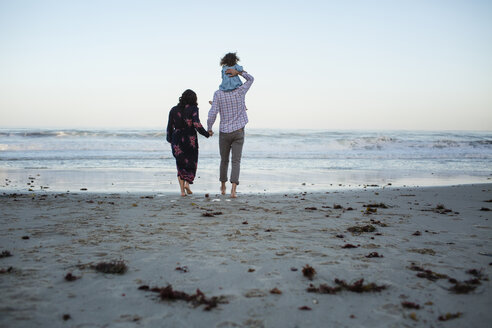 Rear view of man piggybacking daughter while holding woman's hand at beach against clear sky - CAVF21762