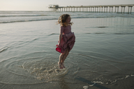 Playful girl jumping in water at beach - CAVF21792