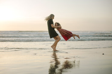 Playful mother spinning daughter against sky at beach - CAVF21801