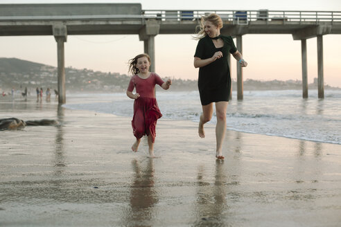 Playful mother and daughter running at beach - CAVF21804