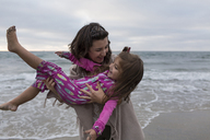Playful mother carrying daughter while standing on shore against sea and sky at beach - CAVF21813