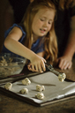Girl putting cookie dough on baking sheet using serving scoop at home - CAVF21897