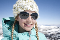 Smiling young woman wearing sunglasses standing against mountains - CAVF21957