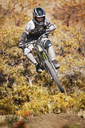 Man mountain biking against trees - CAVF21975