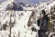 Smiling woman standing against snow covered mountain - CAVF22011
