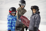 Siblings carrying snowboards while standing on snow covered field - CAVF22017