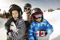 Smiling siblings with snowboards standing on snow covered field - CAVF22020