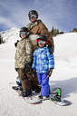 Father and son standing on snowboards on snow covered mountain - CAVF22023