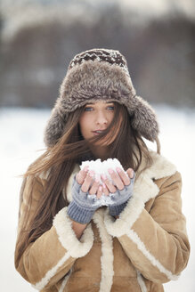 Portrait of beautiful woman wearing warm clothing while holding snow - CAVF22080