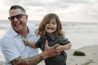 Cheerful father holding son at beach - CAVF22158