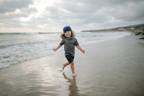 Cheerful boy walking on shore at beach against cloudy sky - CAVF22164
