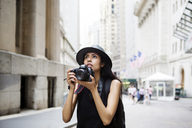 Woman with camera standing on city street - CAVF22239