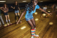 Happy woman enjoying with friends at roller rink - CAVF22281