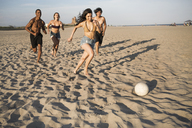 Happy friends playing soccer at beach on sunny day - CAVF22314