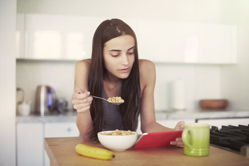 Woman using digital tablet while eating breakfast on table at home - CAVF22329