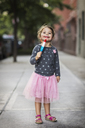 Portrait of cute girl holding ice lolly on footpath - CAVF22407