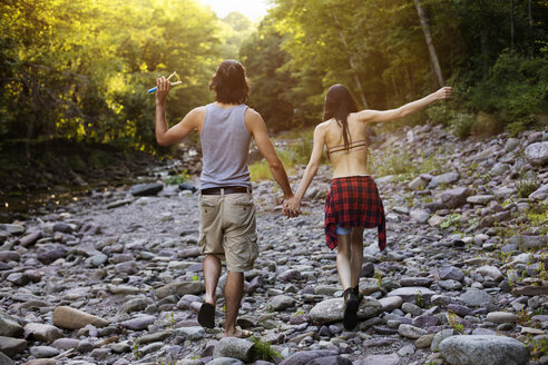 Rear view of couple holding hands while walking on rocks in forest - CAVF22461