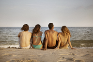 Rear view of friends sitting at beach against sky - CAVF22488