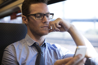 Businessman using smart phone while traveling in train - CAVF22512