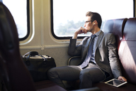 Businessman listening music through tablet computer while traveling in train - CAVF22536