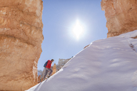 Hiker walking on snow covered mountain at Bryce Canyon National Park during sunny day - CAVF22569