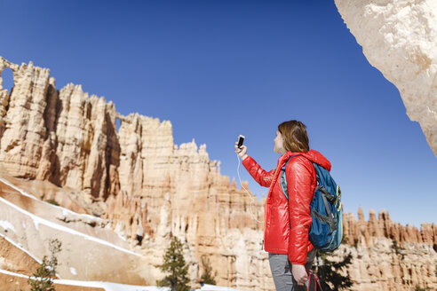 Low angle view of hiker photographing through mobile phone at Bryce Canyon National Park - CAVF22572