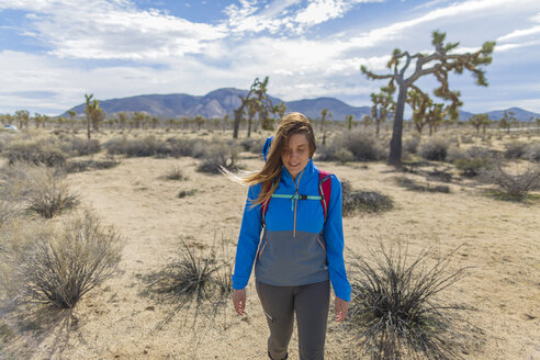 Female hiker with backpack walking on field at Joshua Tree National Park - CAVF22584