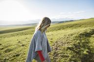 Side view of woman walking on grassy field against sky - CAVF22602