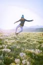 Full length of female hiker jumping on grassy field against sky - CAVF22611