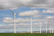 Wind turbines on field against cloudy sky - CAVF22656