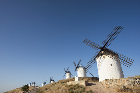 Low angle view of windmills in row against clear sky - CAVF22698
