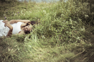 Woman lying on grassy field - CAVF22851