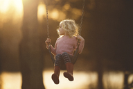 Girl playing on swing at playground during sunset - CAVF22935
