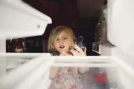 Cute girl looking into refrigerator at home - CAVF22941