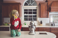 Cute girl playing with banana at table by appliance in kitchen - CAVF22950