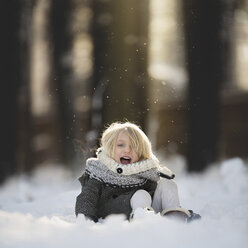 Portrait of cheerful girl playing in snow at park - CAVF22956