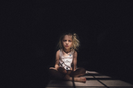 Portrait of thoughtful girl sitting on floor in darkroom during sunny day - CAVF22965
