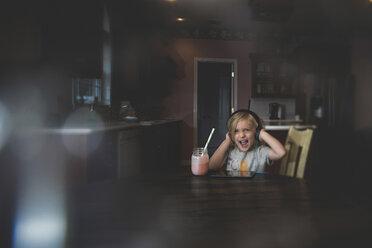 Cheerful girl listening music through tablet computer while having milkshake at table - CAVF22971