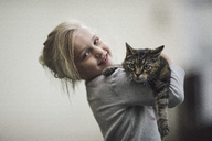 Portrait of cute girl holding tabby cat at home - CAVF22974