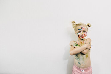 Cute girl covered in messy paint standing against white wall - CAVF22980