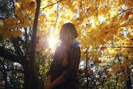 Low angle view of woman standing by autumn tree at park - CAVF23040