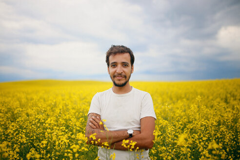 Portrait of confident man standing arms crossed in rapeseed field against sky - CAVF23058
